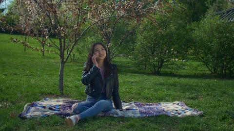 Beautiful asian woman talking on phone in spring park Footage