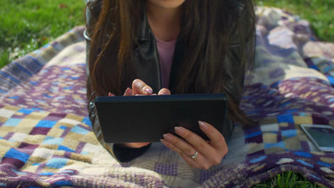 Concentrated asian girl working on tablet pc in park Footage