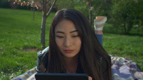 Charming asian girl with tablet pc in spring park Footage