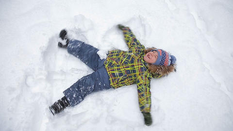 Adorable little boy making snow angel Footage