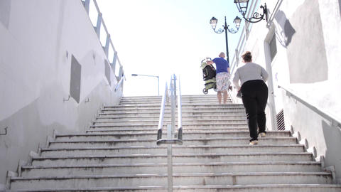 Family with small child and a baby stroller up the steps from the exit of underg Footage