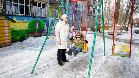 Grandmother and grandson playing in the park in winter Footage