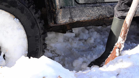 Worker removing snow with a shovel under the a car stuck in drifts of snow 1b Footage