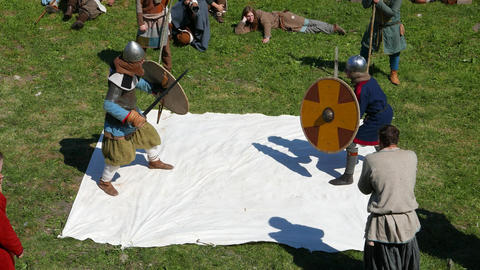 Warrior duel on swords, use round wooden shield to defend. Man aggressively rush Footage
