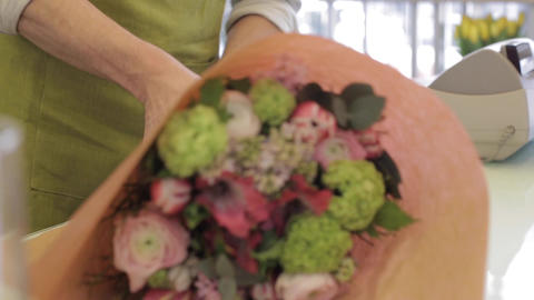 florist wrapping flowers in paper at flower shop Stock Video Footage
