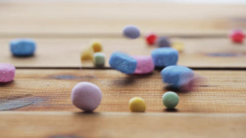 close up of jelly candies falling to wooden table Footage