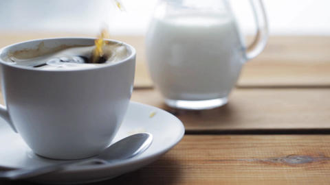sugar falling into cup of coffee on wooden table Footage