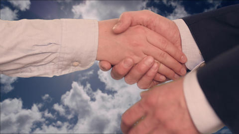 Businessman shaking hands with businesswoman with two hands with cloudy sky on Live Action