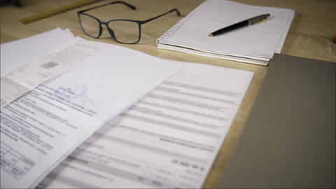 Business document, notebook for notes, ballpoint pen and glasses on table desk Footage