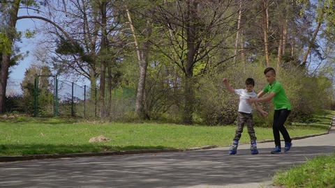 Elder boy help his younger brother to learn to ride on roller skates Footage