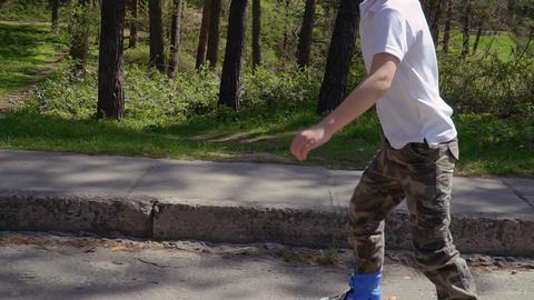 Adorable boy riding on roller skates in summer park Footage