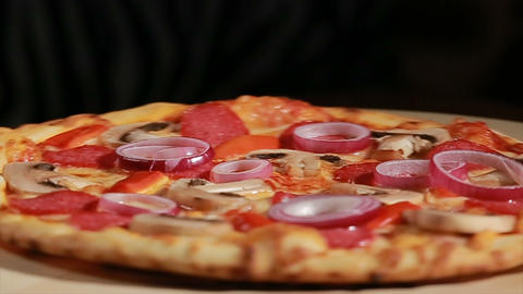 Freshly baked pizza with pepperoni, mushrooms, onion, and pepper turns around Footage