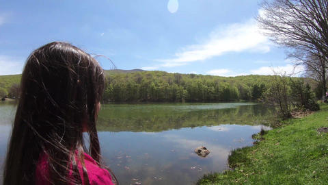 Little girl Standing At Edge Of Lake, Looking At View Of Forest and lake Footage