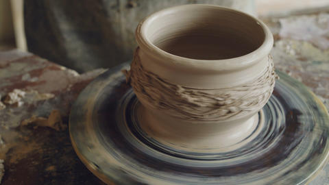 Close-up shot of male hands working with clay on spinning potter's throwing Footage