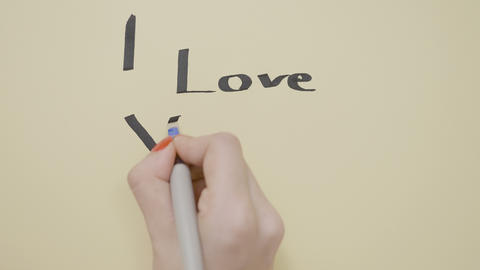 Woman hands writing I love you message for her boyfriend on a piece of paper Footage