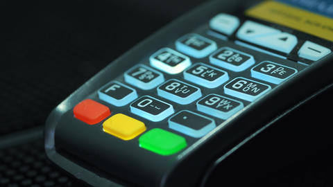 Shop assistant inserting a credit card into a pos and inserting pin-code of the Footage