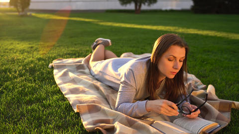 Girl in glasses reading book lying down on a blanket in the park at sunset Footage