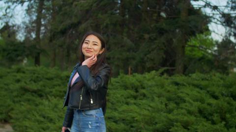 Elegant asian girl turning back smiling in park Footage
