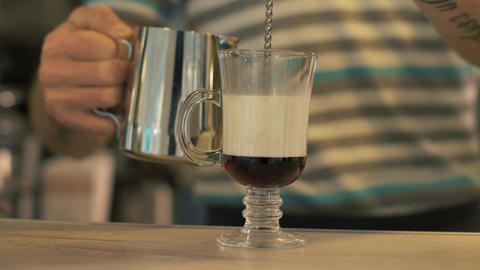 Cafe barista pouring milk in coffee glass cup for preparing latte in coffee shop Footage