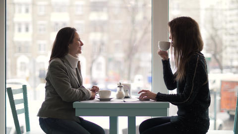 Two woman friends sitting at table and drinking coffee from cup in cafeteria Footage