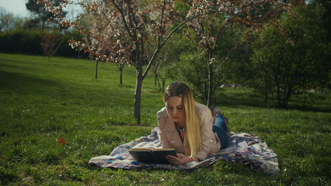 Charming young woman reading a book in spring park Footage