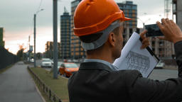 Engineer with the smart phone taking pictures of construction Footage