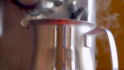 Steaming hot milk in a stainless steel frothing pitcher and coffee dripping in Live Action