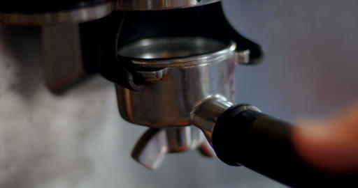 Close up of a hand adding fresh ground coffee and packing it in a portafilter in Live Action