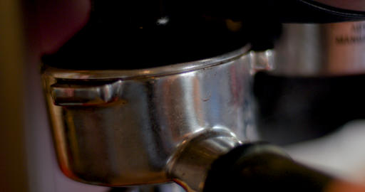 Extreme close up of a hand packing a portafilter with freshly ground coffee in Live Action