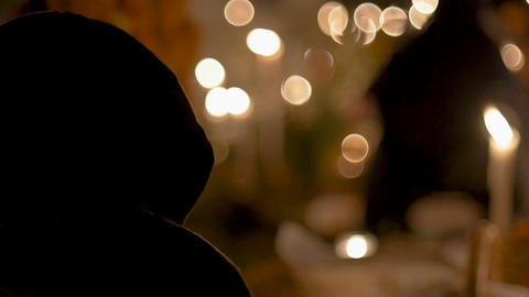 Person covered with a hoodie or scarf sitting by candle light at night in a GIF