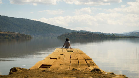 Tourist man relaxing at the edge of a dock alone on a mountain lake on a Footage