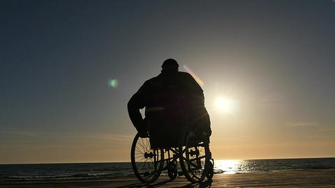 disabled man in wheelchair near sea coast panoramic shot silhouette Footage