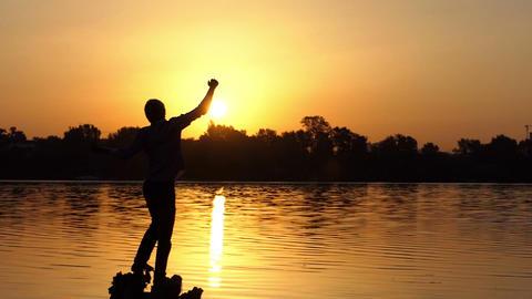 Young man shows a thumb up gesture at a lake in slo-mo GIF