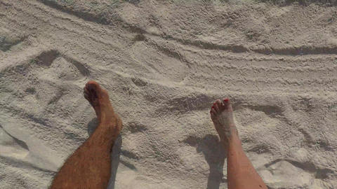 couple feet walking along sandy beach Footage