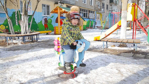 The boy goes for a drive on a swing winter in park Footage