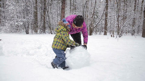 Mother and young son make a snowman in winter park Footage