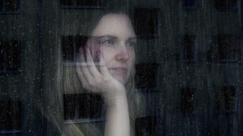 Sad and thoughtful young woman. Looking out through a window Footage