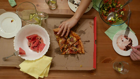 Girl hand slowly take piece of pizza, two remain on desk. Top point view Live Action