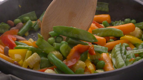 Frying vegetables in black pan Footage