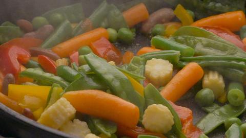 Cooking vegetables on black pan Footage