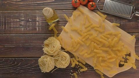 Pasta and ingredients on dark wooden background Footage