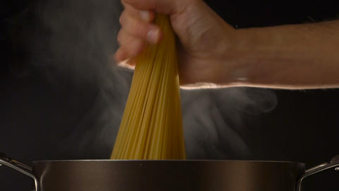 A cook puts down a spaghetti in a steel pot Footage