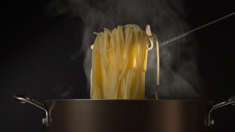 Steaming pasta in a spaghetti spoon on black background Live Action