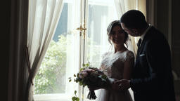 Marrying couple embrace and kiss standing near huge window in room ビデオ