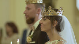 Loving couple standing in the church in crowns with candles in their hands GIF