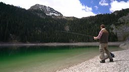 young man cast a spinning on the shores of scenic Lake Footage