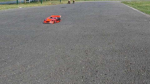 Slow motion. Man drives his high speed scale car towards the camera. Remote Live Action