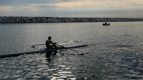 Slow Motion. Silhouette of young rower training rowing on the tranquil sea with Live Action