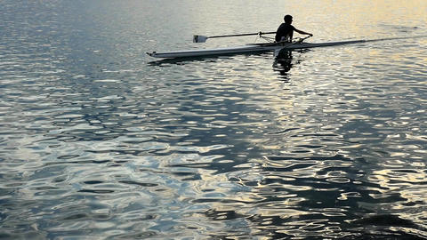 Slow Motion. Silhouette of young rower rowing on the tranquil sunset sea with Live Action