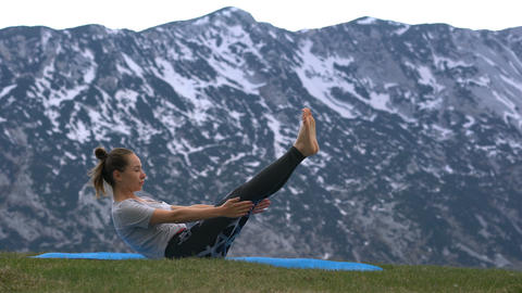 woman practicing yoga outdoors Live Action